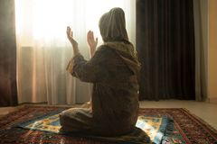 祈祷为阿拉回教神的回教妇女在室在窗口附近 地毯的祈祷在传统佩带的回教妇女的手 库存图片