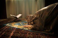 祈祷为阿拉回教神的回教妇女在室在窗口附近 地毯的祈祷在传统佩带的回教妇女的手 免版税库存照片