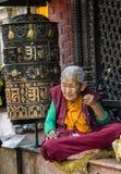祈祷和思考在著名吸引力佛教寺庙Boudhanath Stupa,加德满都,尼泊尔附近的未认出的尼泊尔妇女 库存照片