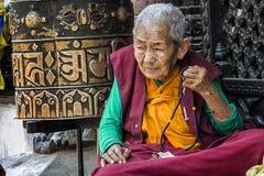 祈祷和思考在著名吸引力佛教寺庙Boudhanath Stupa,加德满都,尼泊尔附近的未认出的尼泊尔妇女 图库摄影