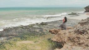 祈祷在一个岩石巴厘岛海滩的印度尼西亚女孩 股票录像