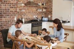 祈祷在一起吃的家庭膳食前在厨房里 库存照片