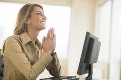祈祷在书桌的愉快的女实业家在办公室 免版税图库摄影