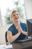 祈祷在书桌的愉快的女实业家在办公室 免版税库存照片