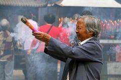 祈祷在佛教徒修道院里的中国年长妇女 免版税库存图片