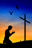 祈祷在十字架下的人 免版税图库摄影