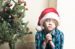 祈祷在圣诞节的哀伤的男孩 免版税库存图片