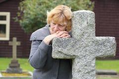祈祷在坟园十字架 免版税库存照片