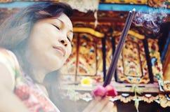 祈祷在寺庙前面的巴厘语妇女 免版税库存图片