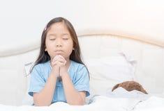 祈祷在床、灵性和宗教上的小女孩 免版税库存照片