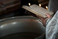 祈祷在教会里的教士拿着霍莉圣经和十字架与蜡烛 免版税库存照片