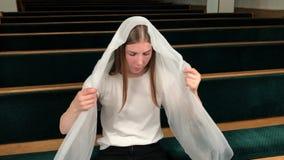 祈祷在施洗约翰教堂里的年轻宗教虔诚妇女 欧洲大教堂的忠实的天主教徒:圣地的里面 股票录像