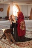 祈祷在有古兰经的清真寺的年轻回教妇女 图库摄影