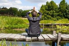 祈祷在木道路的商人瑜伽水面上 库存照片