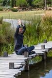 祈祷在木道路的瑜伽40s商人在水附近 库存照片