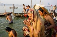 祈祷在河岸的人群的资深妇女 库存照片