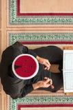 祈祷在清真寺里面的一个宗教回教人的顶视图 免版税库存照片