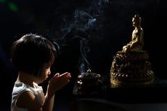 祈祷在菩萨前面的亚裔矮小的中国女孩 库存图片