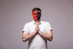 祈祷在阿尔巴尼亚国家队比赛的阿尔巴尼亚足球迷在灰色背景的 库存图片