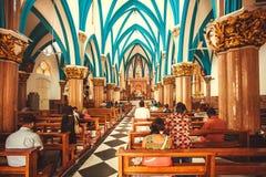 祈祷在17世纪宽容圣玛丽` s大教堂里面的人们 免版税库存照片