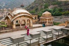 祈祷在18世纪寺庙的储水箱的附近印度妇女 库存照片