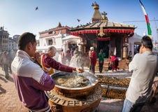 祈祷在Bodnath stupa附近的人们 免版税库存图片