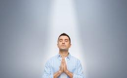 祈祷在ligh下光芒的人  免版税库存照片