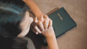 祈祷夜的女孩 女孩手祈祷 女孩圣经在她的手上祈祷与圣经 的treadled 股票视频