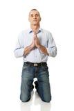 祈祷对膝盖的上帝的成熟人 库存图片