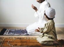 祈祷沿着他的父亲的小男孩在赖买丹月期间 免版税库存照片