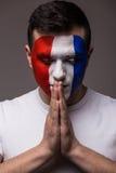 祈祷法国在法国国家队比赛的足球迷与接近的眼睛的 免版税库存照片