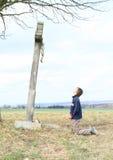 祈祷由与耶稣的十字架的男孩 图库摄影