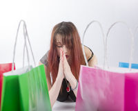 祈祷由五颜六色的购物袋的少妇 免版税库存照片