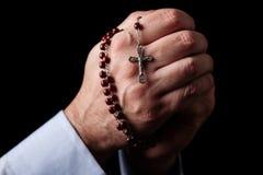 祈祷男性的手拿着有耶稣基督的一个念珠十字架或耶稣受难象的在黑背景 免版税库存图片
