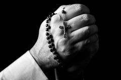 祈祷男性的手拿着有耶稣基督的一个念珠十字架或耶稣受难象的在黑背景 图库摄影
