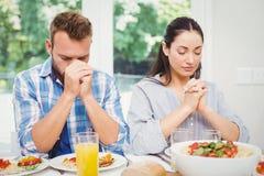 祈祷的夫妇,当坐在餐桌上时 免版税库存照片