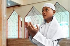 祈祷里面清真寺的亚洲回教孩子 图库摄影