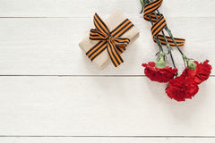 祖国保卫者日 红色康乃馨和礼物盒与 图库摄影