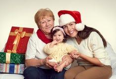 祖母、女儿和孙女在帽子与礼物盒坐沙发的圣诞老人,白色背景穿戴了 除夕和圣诞节 库存照片