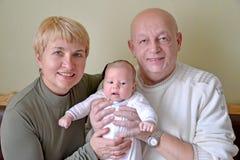 祖母、祖父和婴孩 3个照相机长沙发系列女孩查找关于坐的母亲橙色纵向他们那里 库存照片