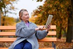 祖母与片剂坐一条长凳在秋天公园 库存照片