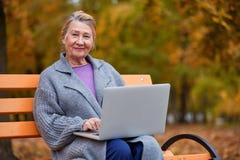 祖母与膝上型计算机坐一条长凳在秋天公园 图库摄影