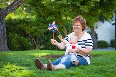 祖母和使用与在绿色草坪的轮转焰火的男婴 库存照片