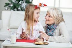 祖母和女孩有看的Cardpaper的 免版税库存图片