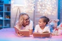 祖母和孙女在家是阅读书在睡眠前在晚上 图库摄影