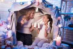 祖母和孙女在晚上在家吃着曲奇饼用牛奶在一揽子房子里 库存照片