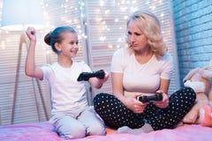 祖母和孙女在晚上在家打电子游戏 女孩赢取 图库摄影