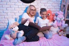 祖母和孙女在晚上在家读lange书 免版税库存图片