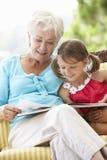 祖母和孙女在车顶上的座位的阅读书 库存图片