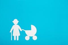 祖母和孩子纸板形象在蓝色背景 的treadled 库存照片